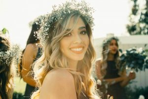young woman at a wedding with a flower crown smiling