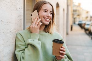 young woman smiling while on the phone and holding a coffee cup