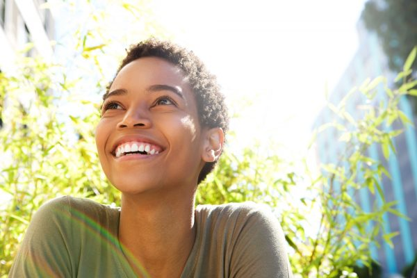 woman with short hair and dark skin smiling while looking up outside