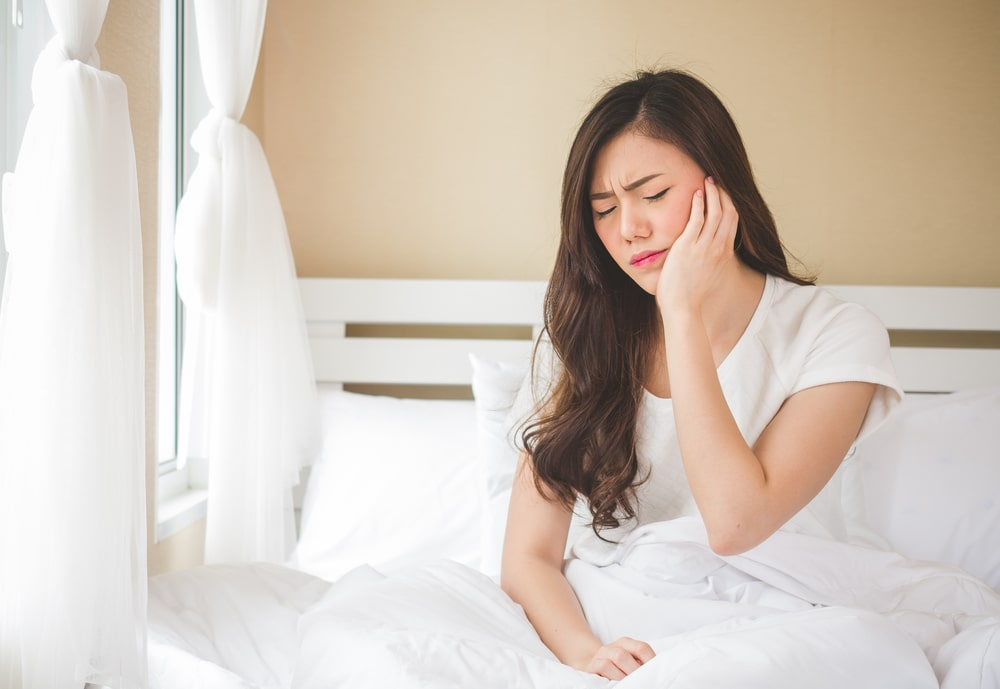 woman with jaw pain in bed