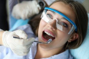 young female patient getting her teeth cleaned